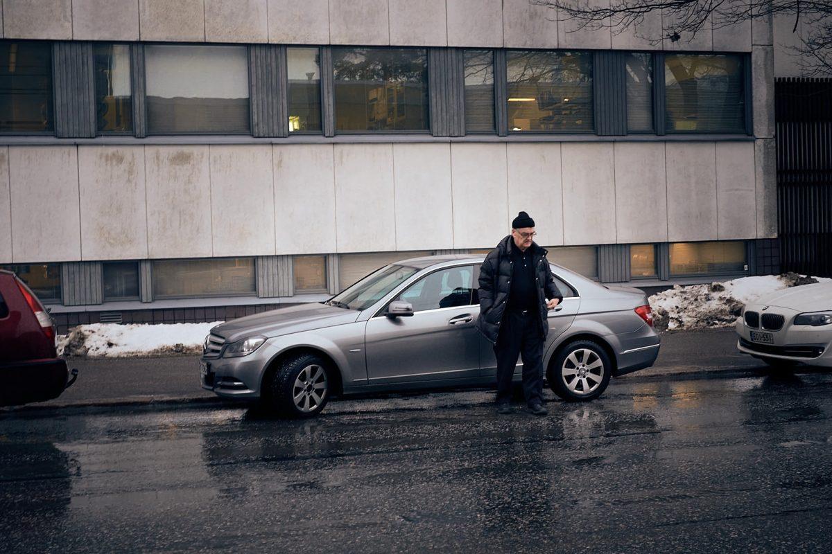 Mies seisoo auton vieressä sateessa.
